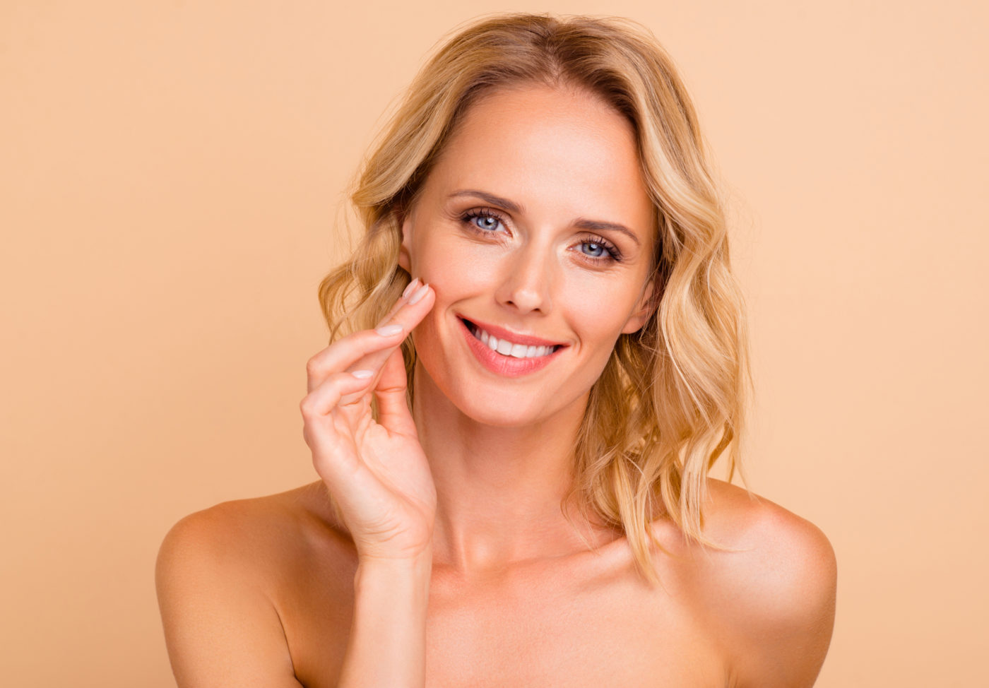 Salon spa therapy treatment concept. Close-up portrait of attractive cheerful wavy-haired lady with flawless smooth pure clean clear skin applying cream on cheek isolated on beige background.