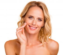 Salon spa therapy treatment concept. Close-up portrait of attractive cheerful wavy-haired lady with flawless smooth pure clean clear skin applying cream on cheek isolated on beige background